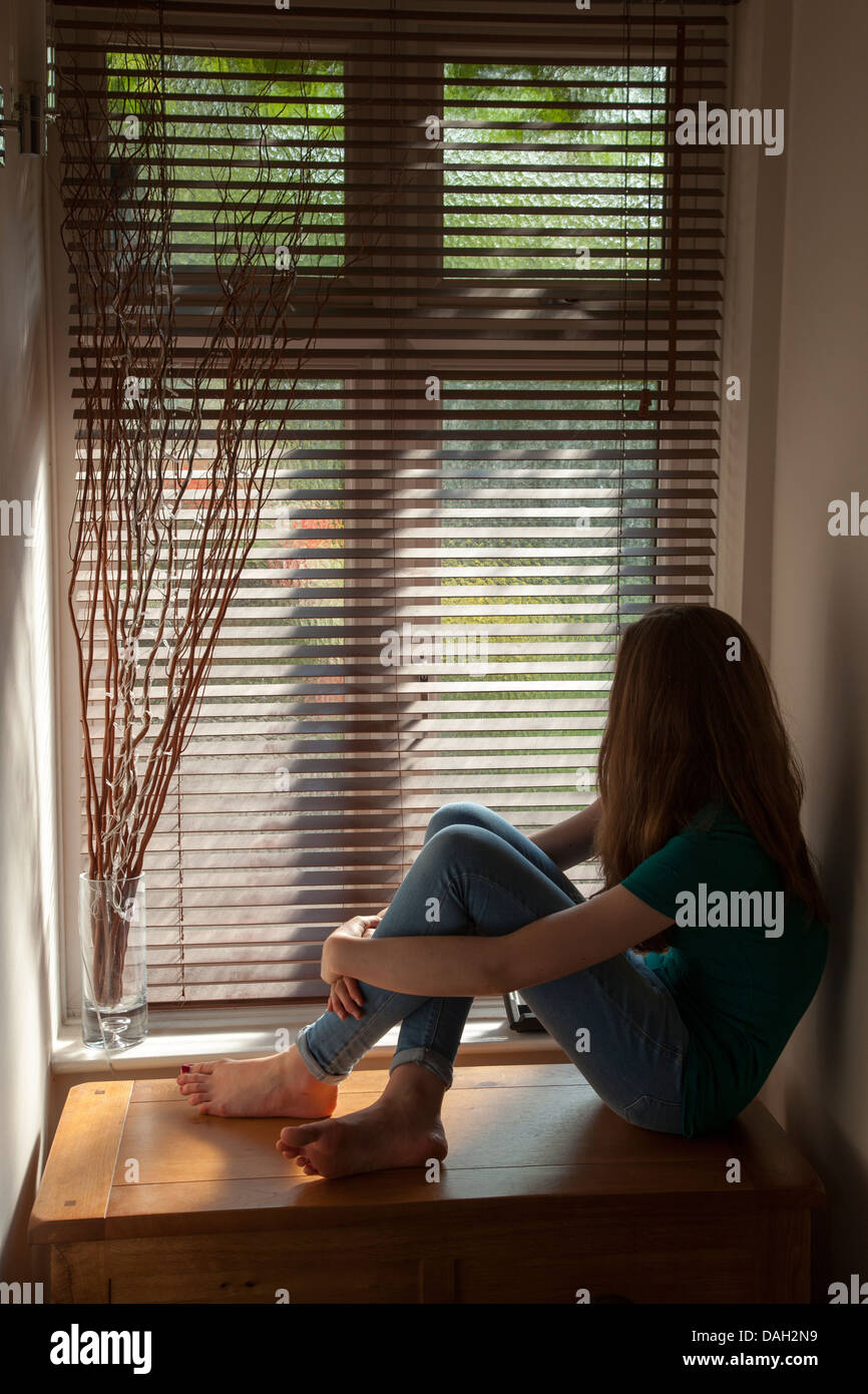 A teenage girl, sitting in darkness by a window with light outside. - Stock Image