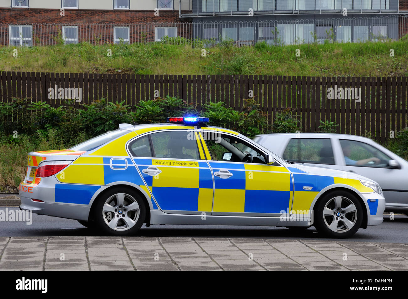 Police car with blue and yellow hi vis checkered livery Stock Photo