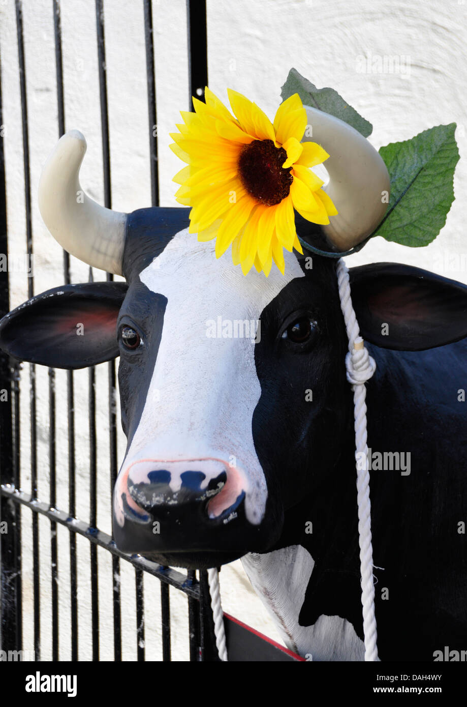 Oxon - Thame - in the Buttermarket - life size model of a black and white cow - with a flower behind her ear - Stock Image