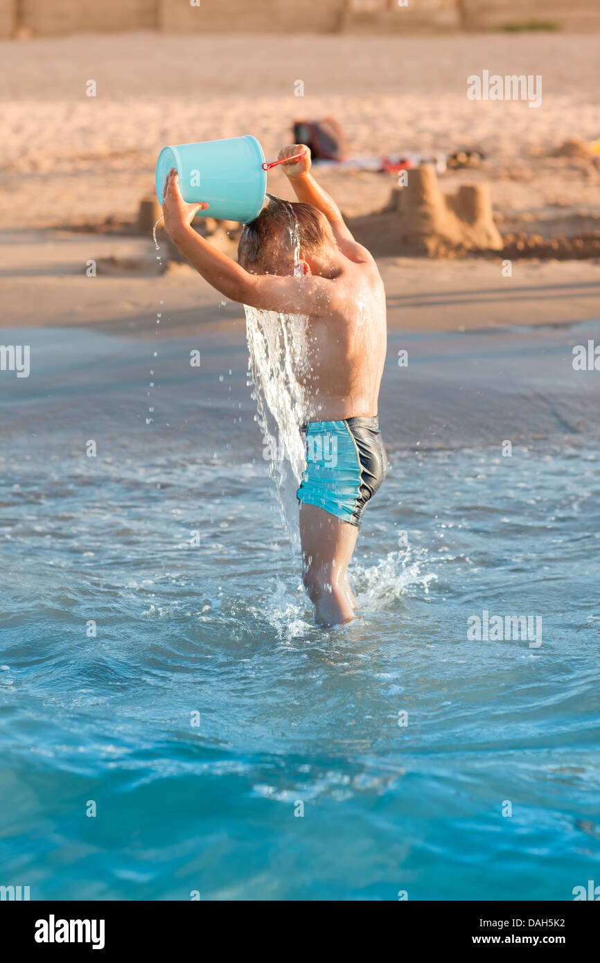 Hot summer - little boy splashing on the beach - Stock Image