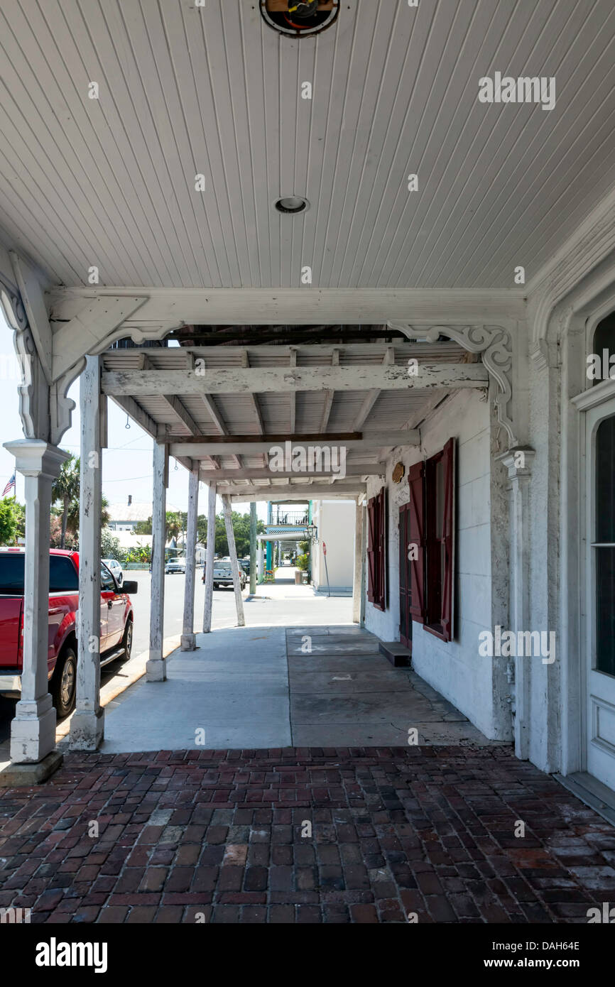 View of 2nd street from covered sidewalk in the historic business district of Cedar Key, Florida. Red pick-up truck - Stock Image
