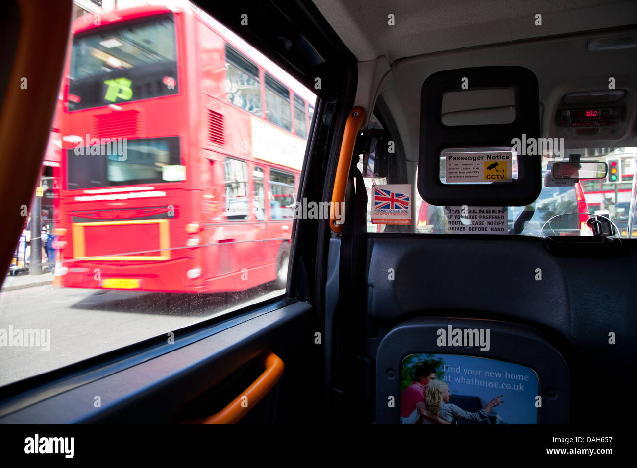 View from inside taxi looking at London red bus going by. - Stock Image