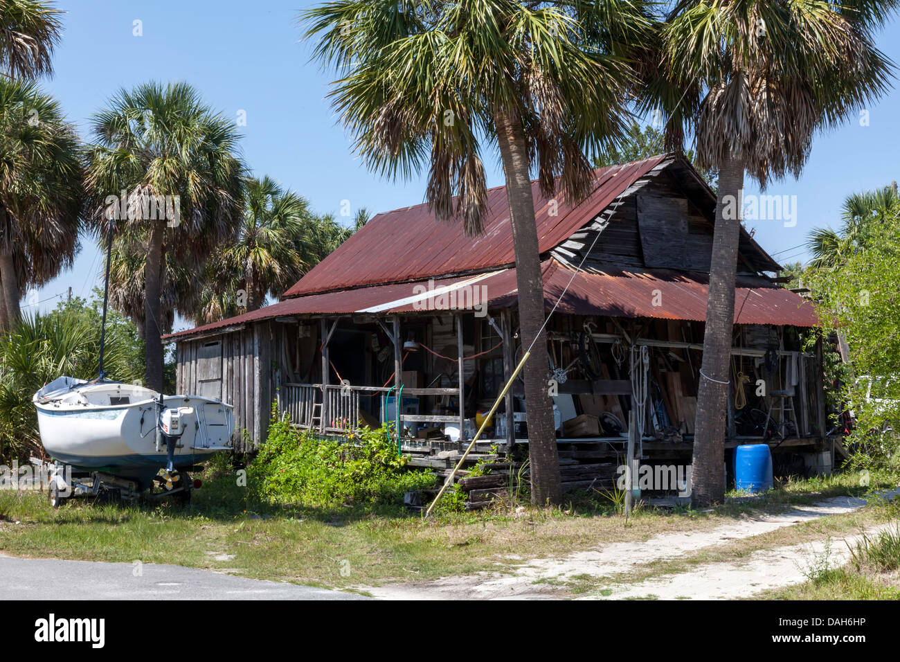 An old rundown wood frame house with rusting metal roof . A sailboat on a trailer and junk clutter the porch and - Stock Image