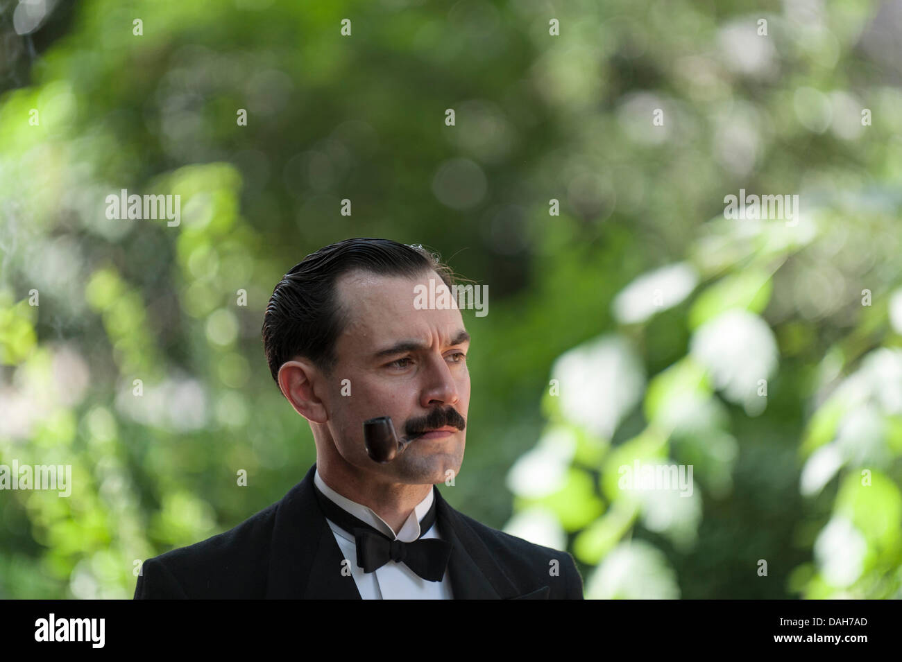 London, UK. 13 July 2013.  A pipe smoking gentleman waits for the start of the 2013 Chaps Olympiad in Bedford Square - Stock Image