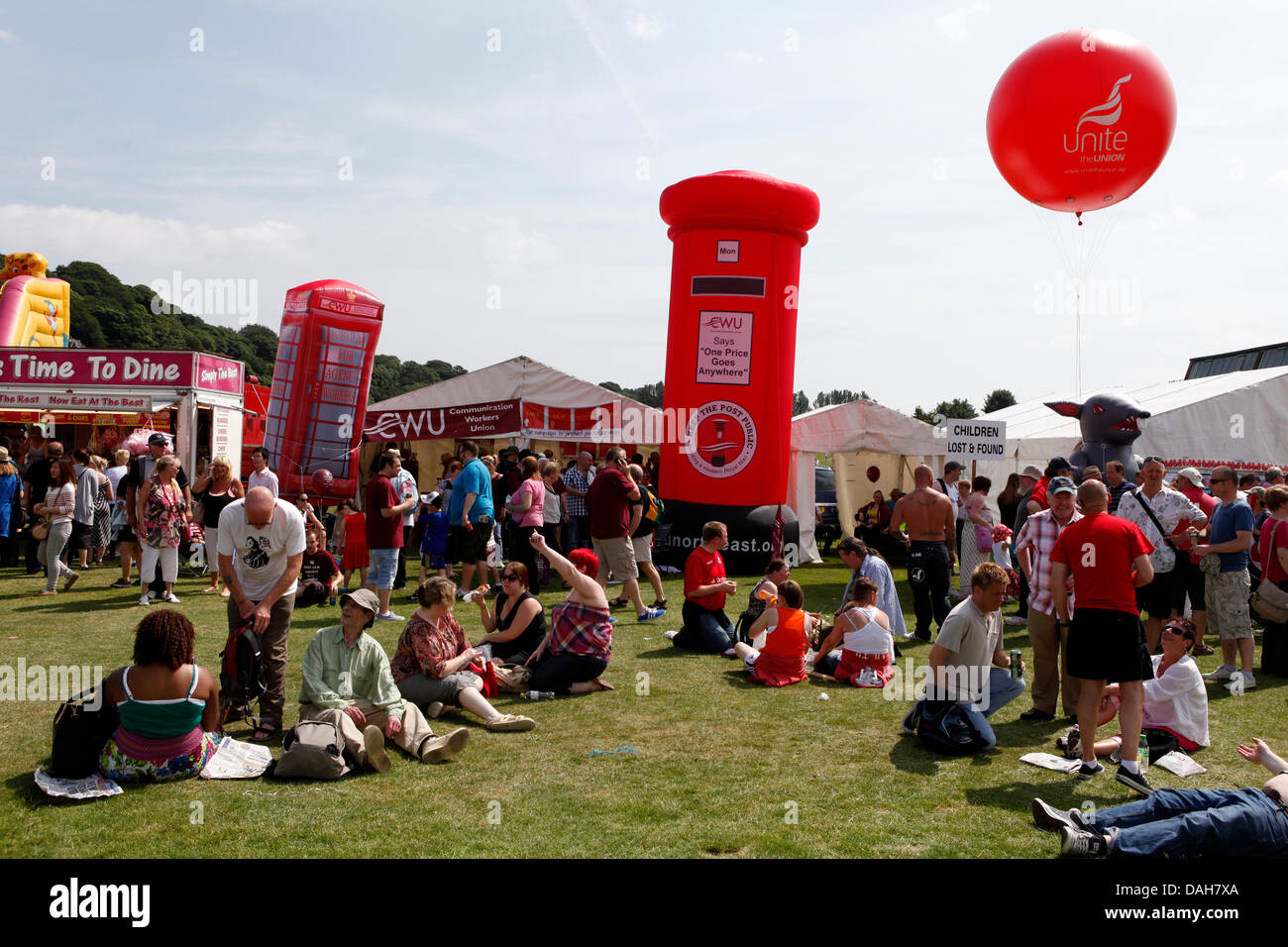 People enjoy sunshine at the 129th Durham Miners Gala at Durham, England. The CWU tent is seen in the background. - Stock Image