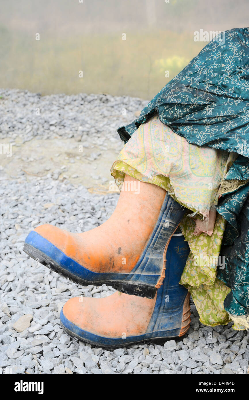 Orange and blue steel toe capped chainsaw protective safety boots worn with colourful silk skirts, Wales, UK - Stock Image