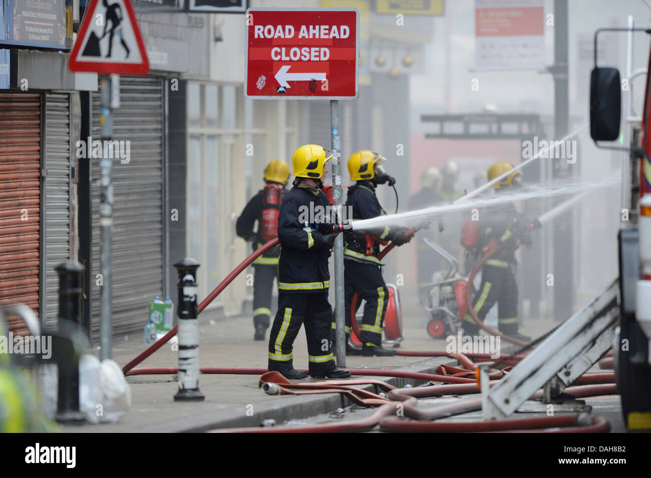 Manchester, UK. 13th July, 2013. Firefighters tackle a blaze at Paul's Hair World and NQ Life music venue on - Stock Image