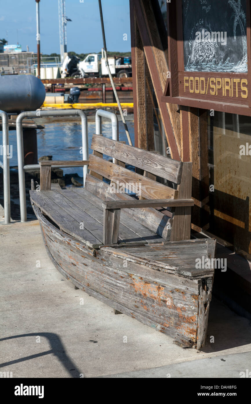 Beat up wooden boat-shaped bench in front of a waterfront establishment advertising food and spirits. Dock construction - Stock Image