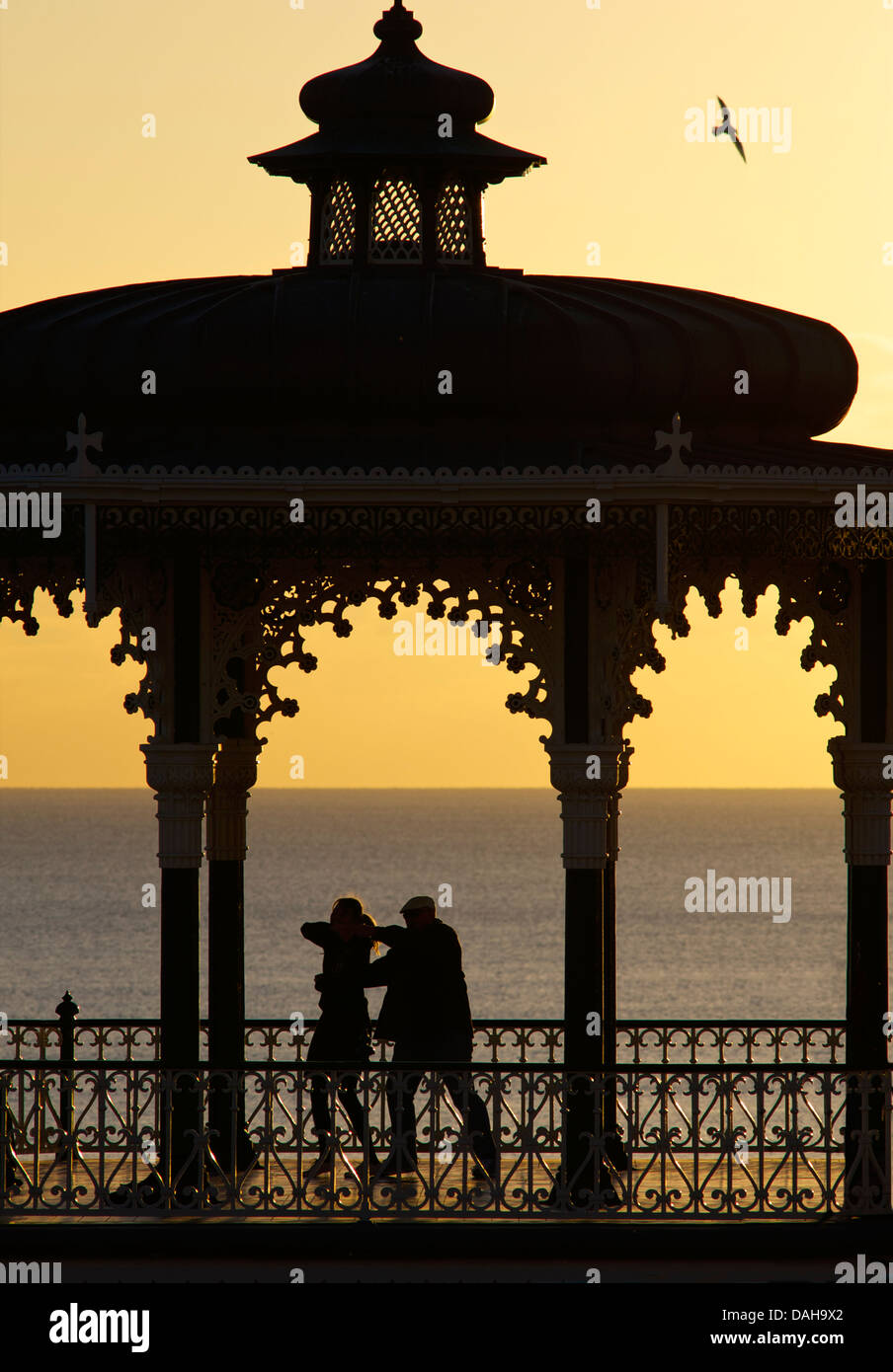 Silhouetted couple dancing on the Victorian bandstand, Brighton seafront. East Sussex, England - Stock Image