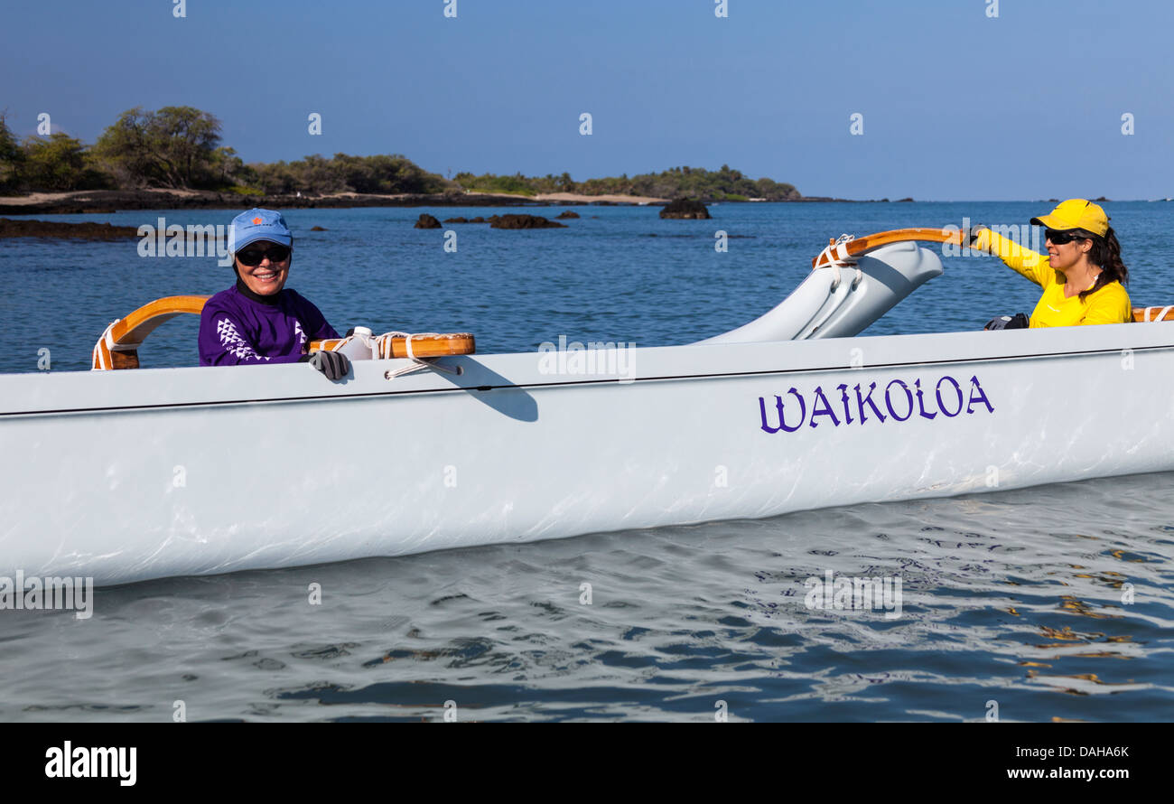 Women hold outrigger canoe in Anaehoomalu Bay in Waikoloa on the Big Island of Hawaii before paddling adventure - Stock Image