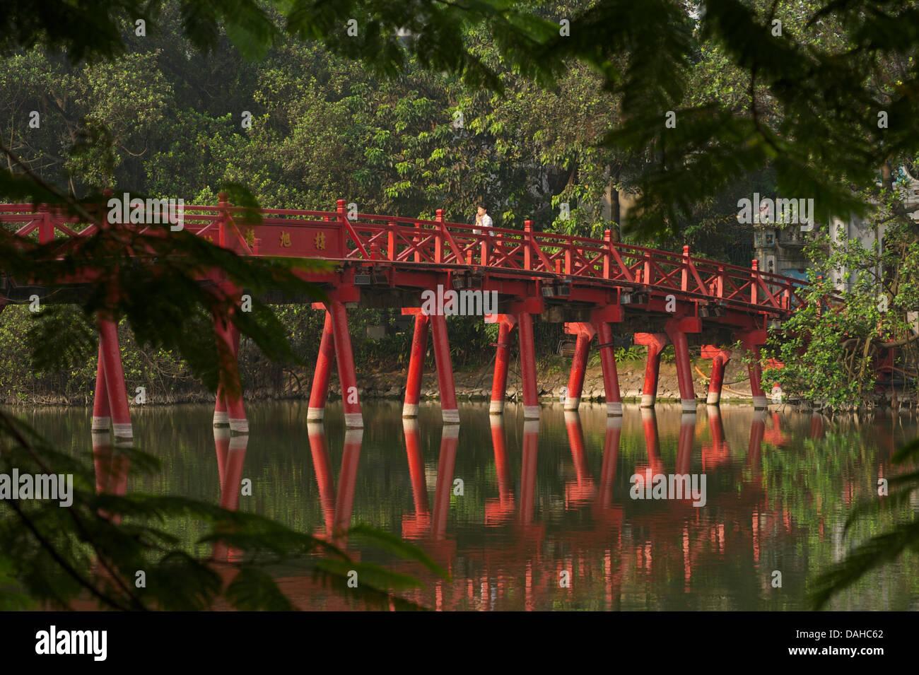 Woman praying as she crosses The Huc Bridge, Hoan Kiem Lake, Hanoi, Vietnam - Stock Image