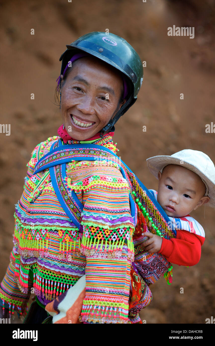 Flower Hmong woman with child  in distinctive tribal costume. Can Cau, Near Bac Ha.  Vietnam. Model released - Stock Image