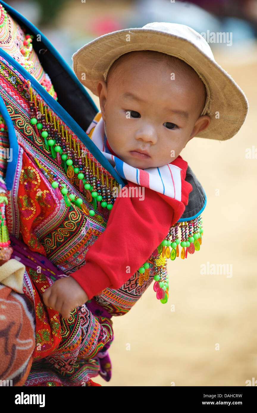 Flower Hmong child carried on mother's back. Distinctive tribal costume. Can Cau, Vietnam. Model released - Stock Image