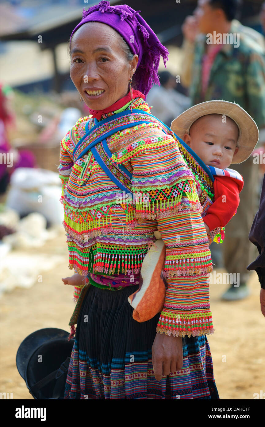 Flower Hmong woman with child  in distinctive tribal costume. Can Cau, Vietnam. Model released - Stock Image