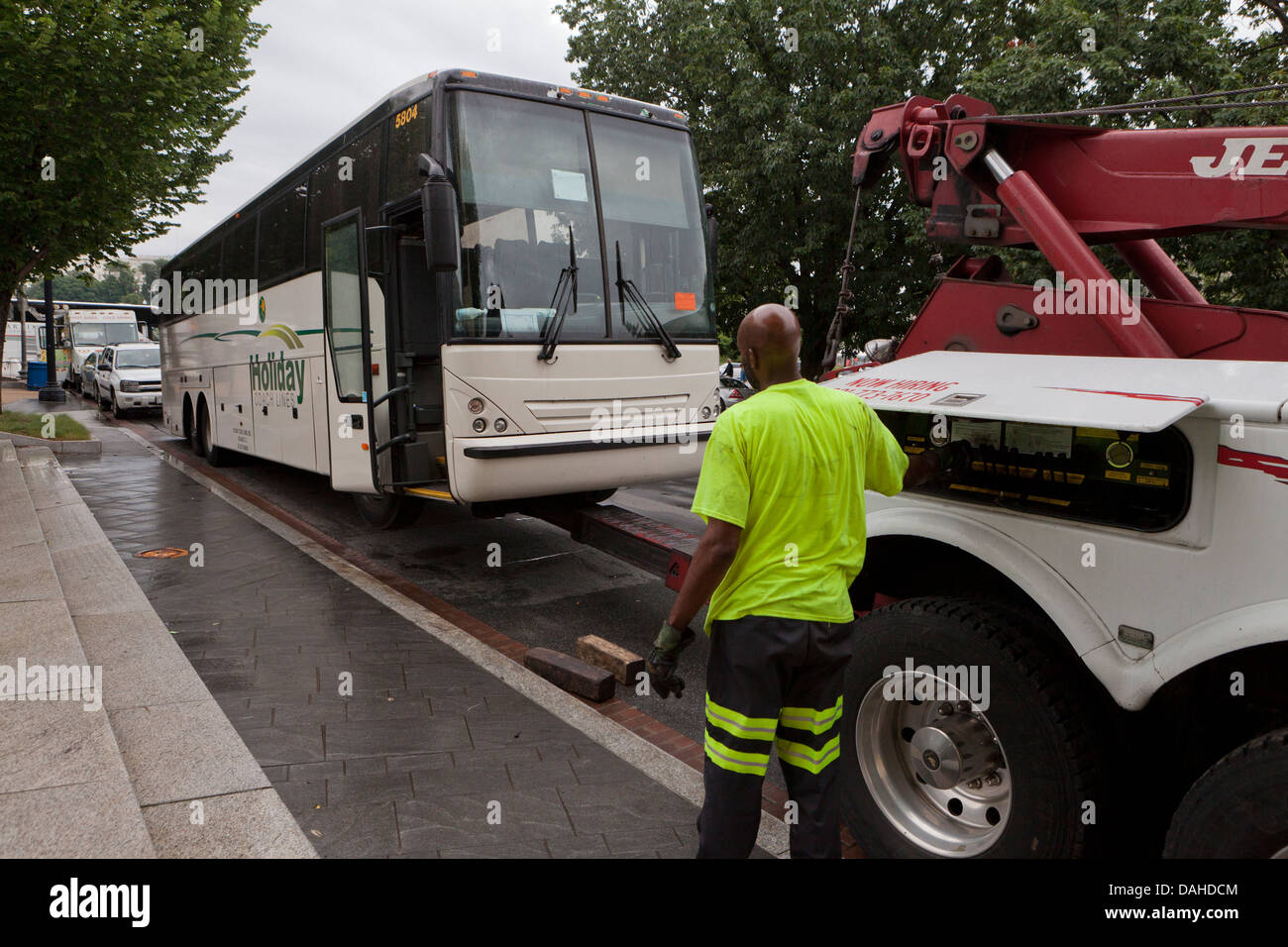 Disabled tour bus getting towed - Stock Image