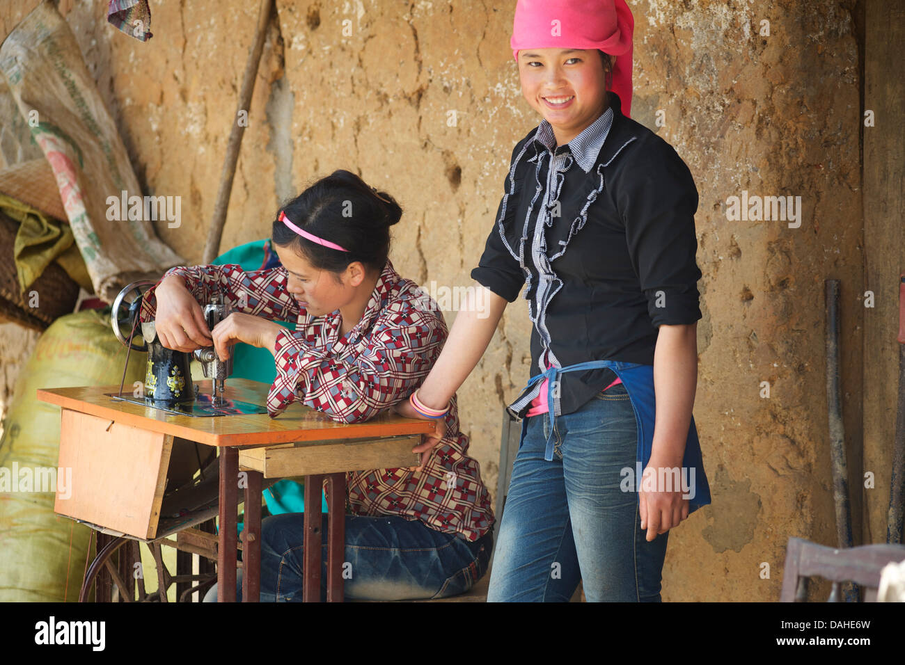 Hilltribe women, one using a sewing machine, Lung Phin between Bac Ha and Can Cau, N Vietnam - Stock Image