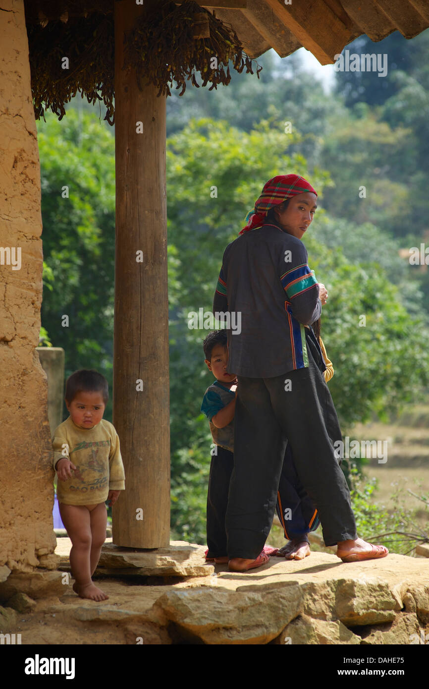 Father and children outside their home in the hilltribe community of Lung Phin between Bac Ha and Can Cau,  N Vietnam - Stock Image