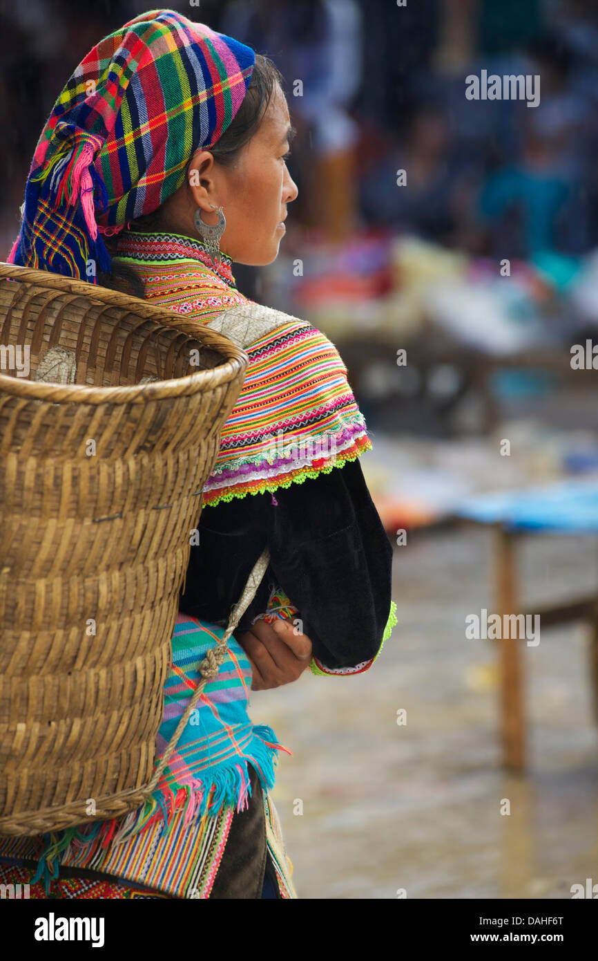 Flower Hmong woman in distinctive tribal dress with carry basket on back. Bac Ha market, Lao Cai province, Vietnam - Stock Image