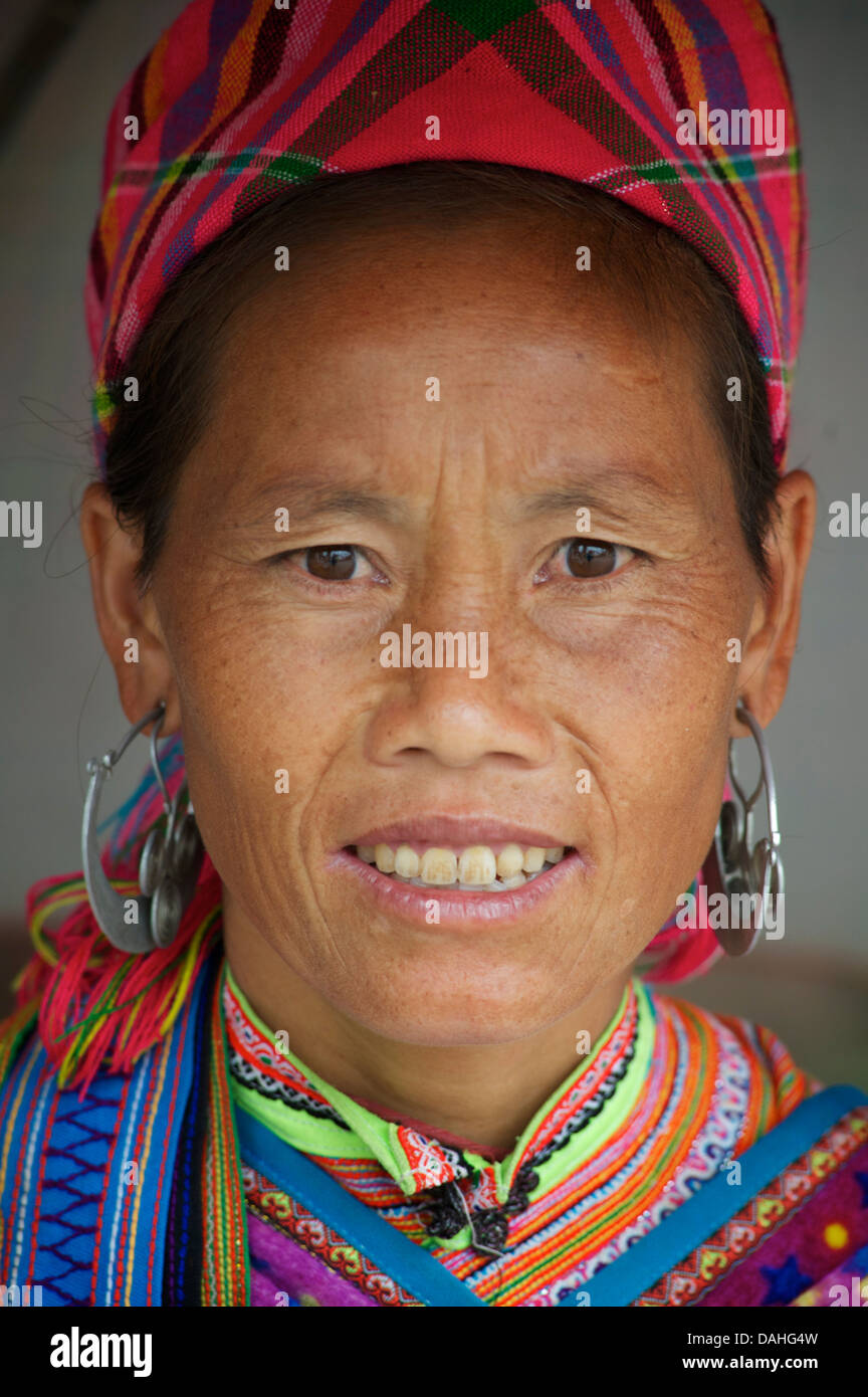 Potrait of a Flower Hmong woman in her brightly embroidered tribal costume, Bac Ha market, N Vietnam. Model Released - Stock Image