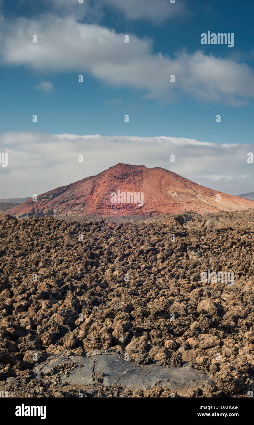 Aa lava field with small area of black pahoehoe in the foreground, and Montana Bermeja, southern Lanzarote, in the - Stock Image