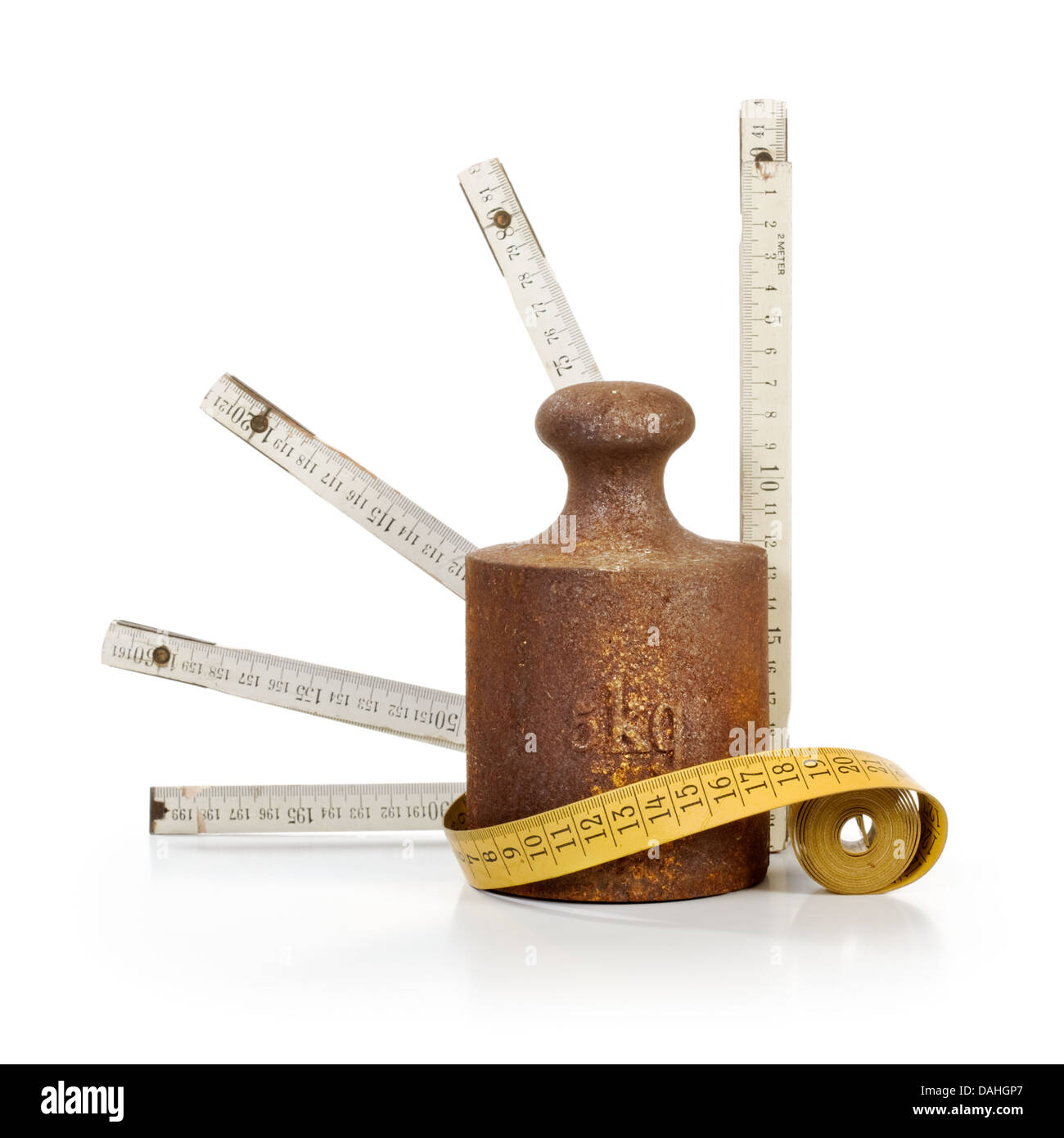 Old rusty weight, tape measure and yardstick on white background - Stock Image