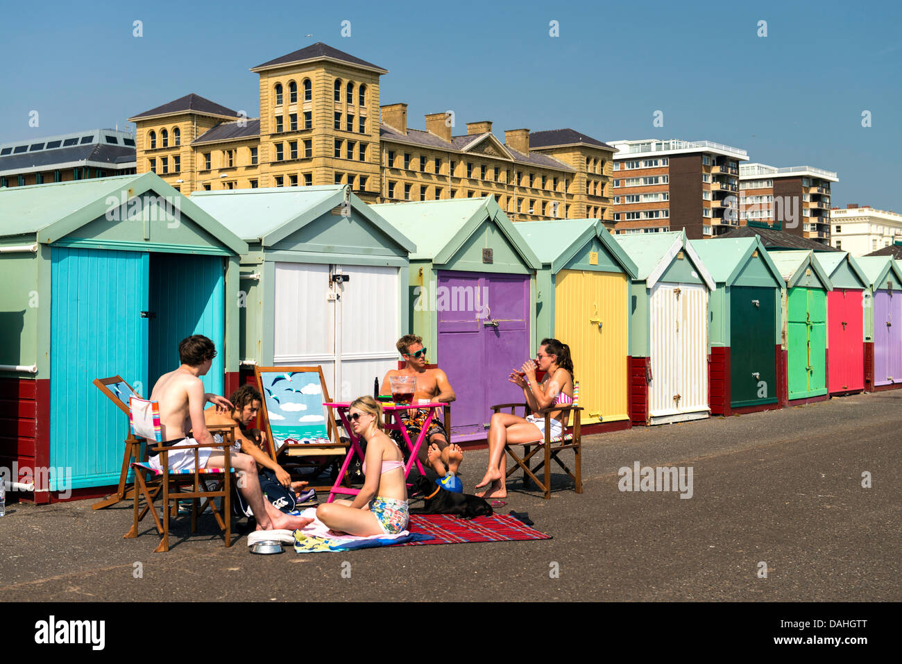 Young Brits enjoying the sun by the beach huts in Summer Brighton England Great Britain UK - Stock Image