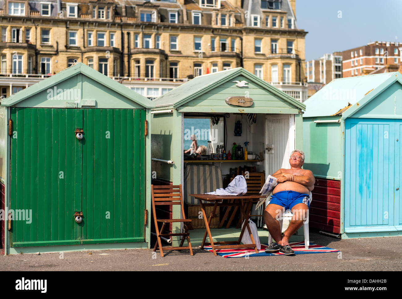Old Man Basking In The Sun By Beach Huts In Brighton England Great