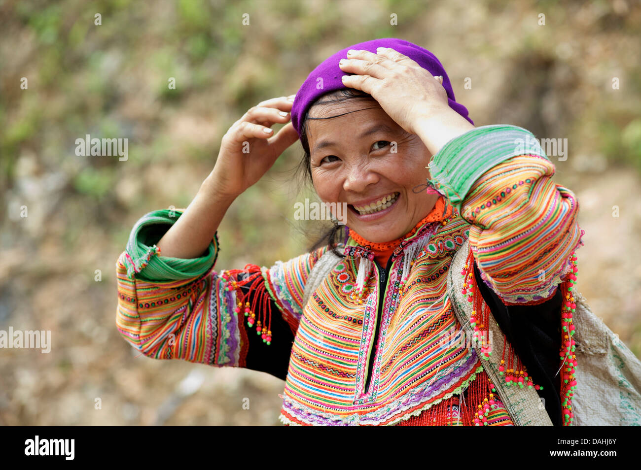 Potrait of a Flower Hmong woman in her brightly embroidered tribal costume, Coc Ly market, N Vietnam. Model Released - Stock Image