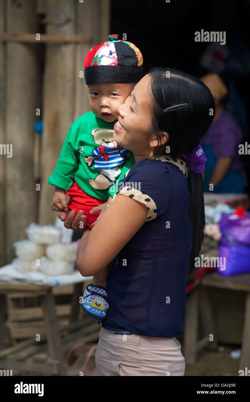Vietnamese woman carrying young boy. Coc Toc village, Near Ba Be, Northeast Vietnam - Stock Image