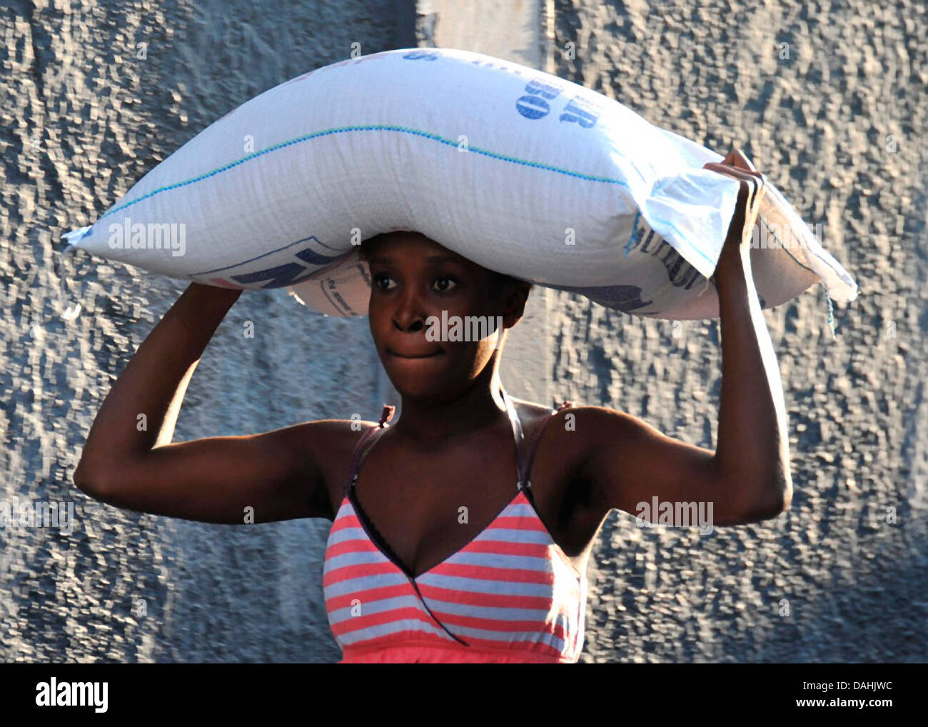A Haitian woman carries a 55-pound bag of rice distributed by the World Health Organization at a food distribution Stock Photo