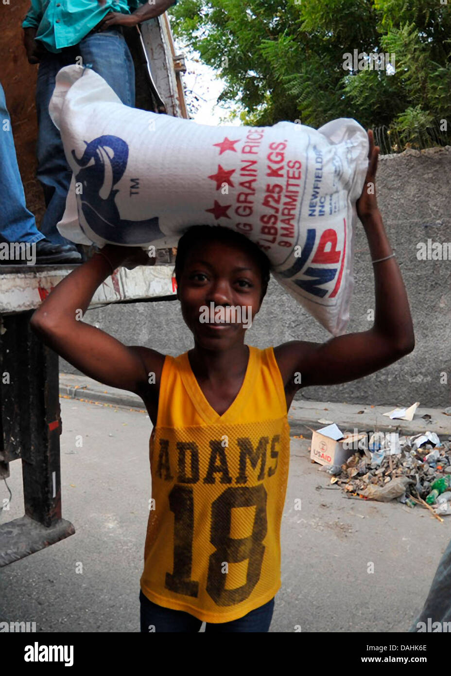 A young Haitian woman carries a 55-pound bag of rice distributed by the World Health Organization at a food distribution - Stock Image