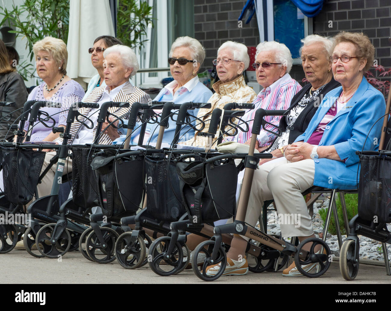 Eight old women sit in front of a senior residence with their rollators / wheeled walkers / walking aid in front - Stock Image