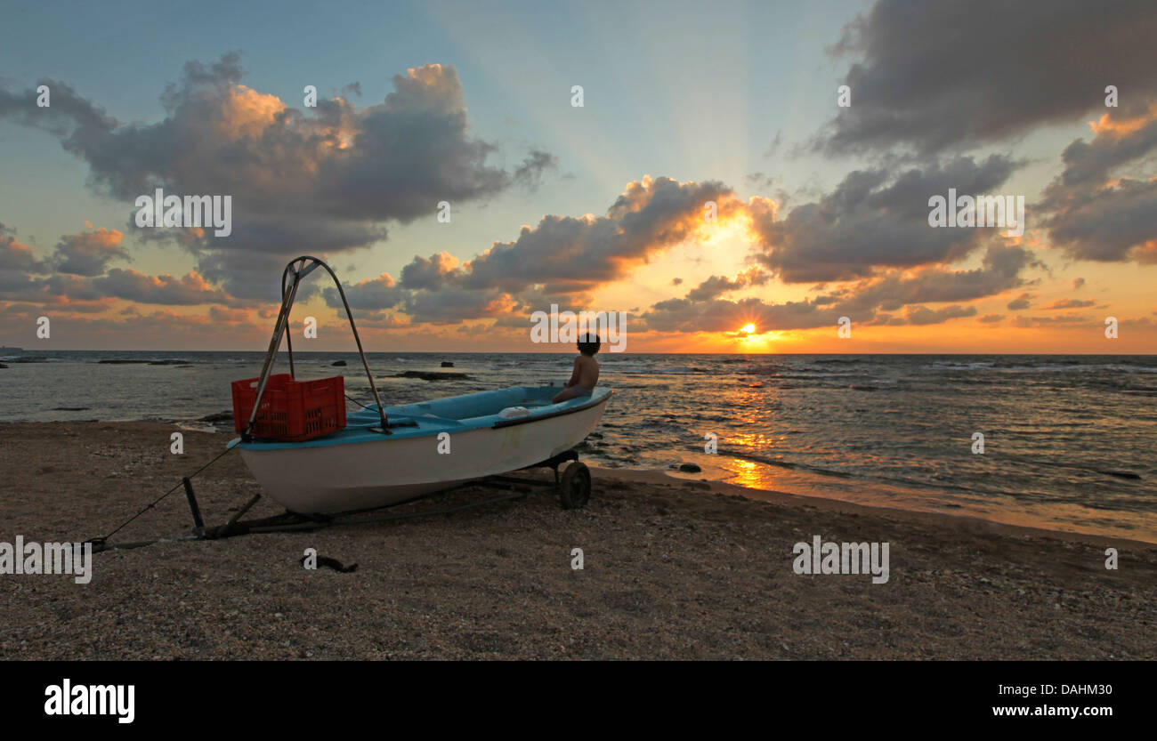 Beached fishingboat at sunset On the beach near Acre, Israel - Stock Image