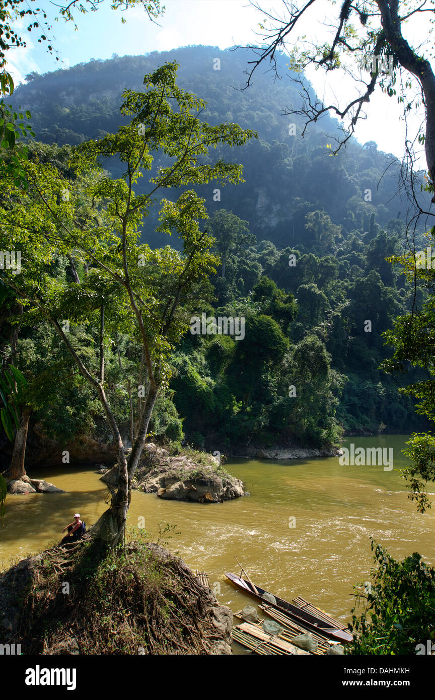European tourist sitting under a tree downstream of Dau Dang Waterfall, Ba Be National Park, Northeast Vietnam - Stock Image