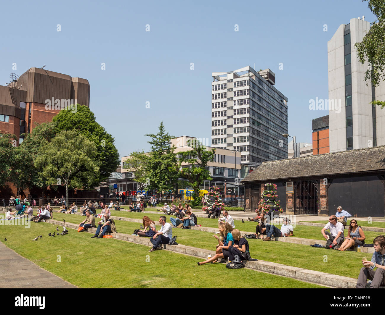 Office workers take a lunch break in Merrion Gardens Leeds West Yorkshire UK - Stock Image