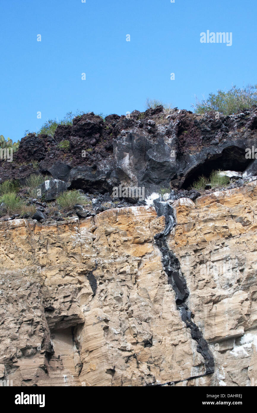 Volcanic dike formed when lava was forced into a crack through older tuff (compacted volcanic ash) formation - Stock Image