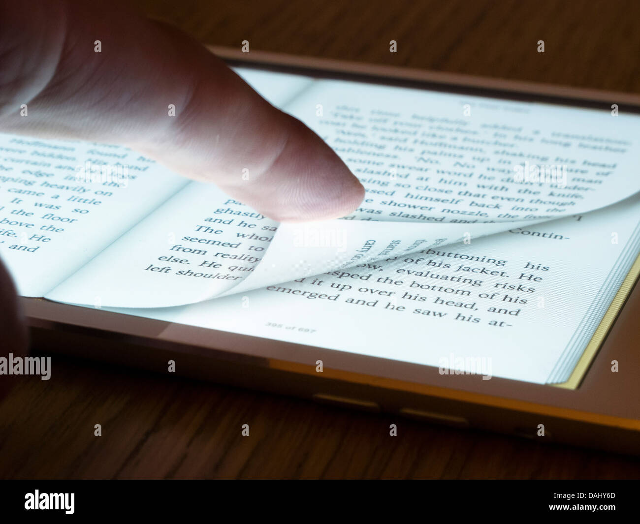 Turning page of ebook reader on an iPad mini tablet computer - Stock Image