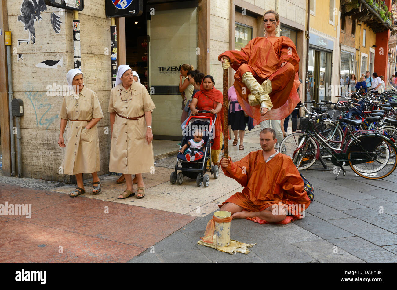 Street mime artists watched by nuns in Verona Italy - Stock Image