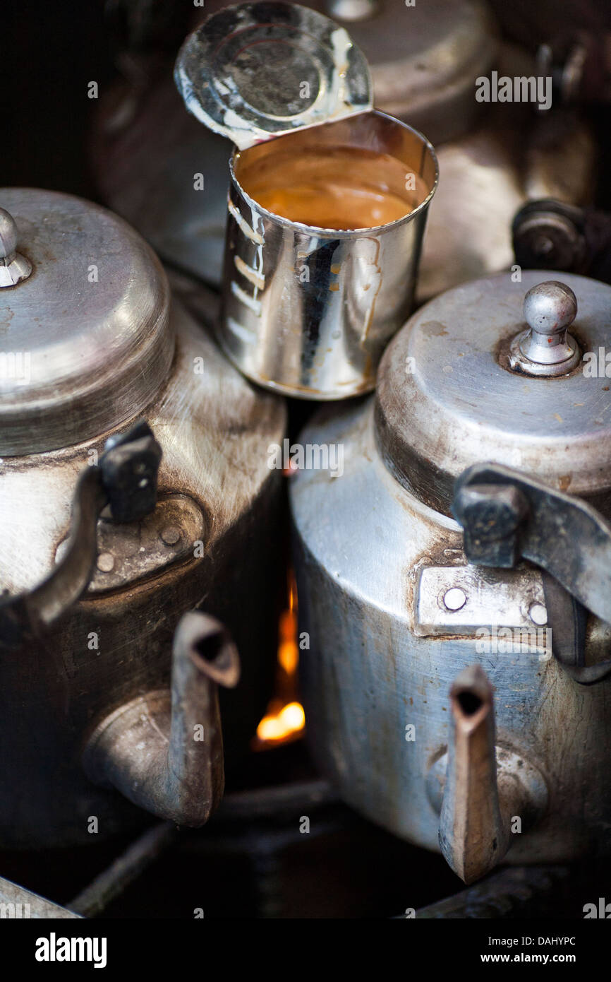 Traditional milky white tea and tea pots and tin can heat up on a stove in the historic old city of Dhaka Bangladesh. - Stock Image