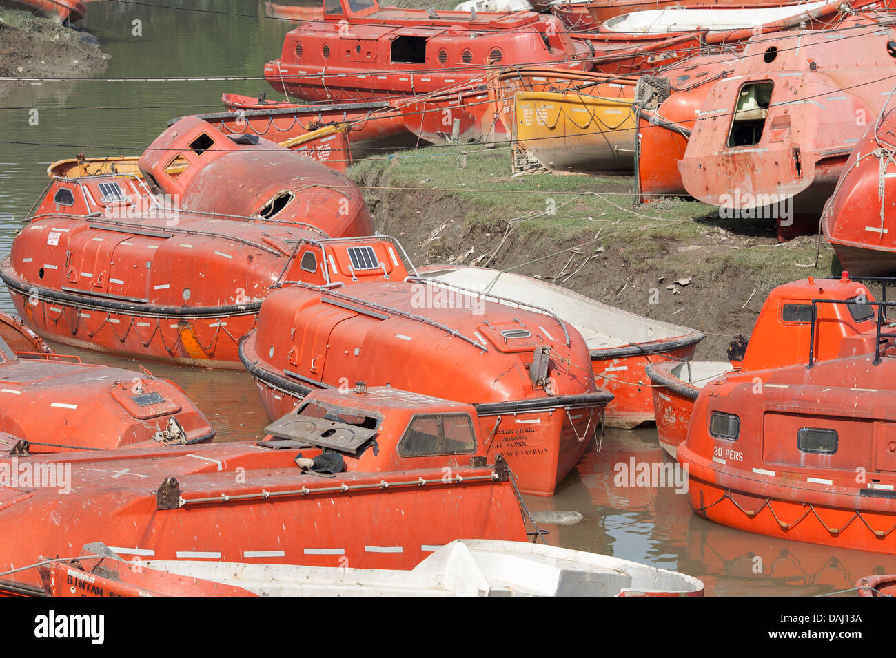 Old discarded bright orange life boats from ships for sale close to ...