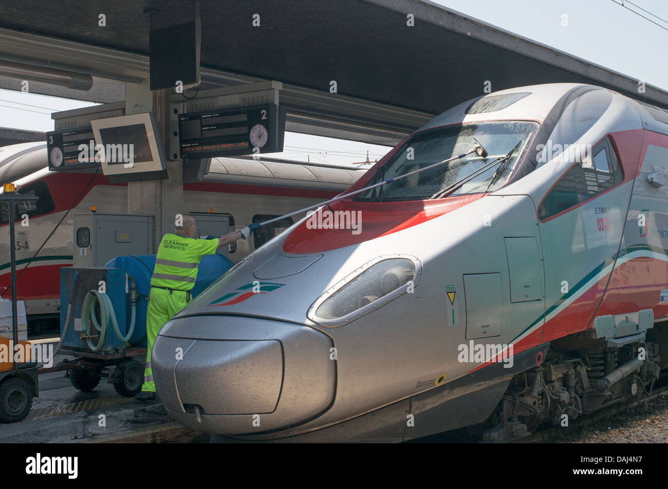 Man cleaning windscreen of Trenitalia ETR610 Frecciargento high speed train in Venice railway station Stock Photo