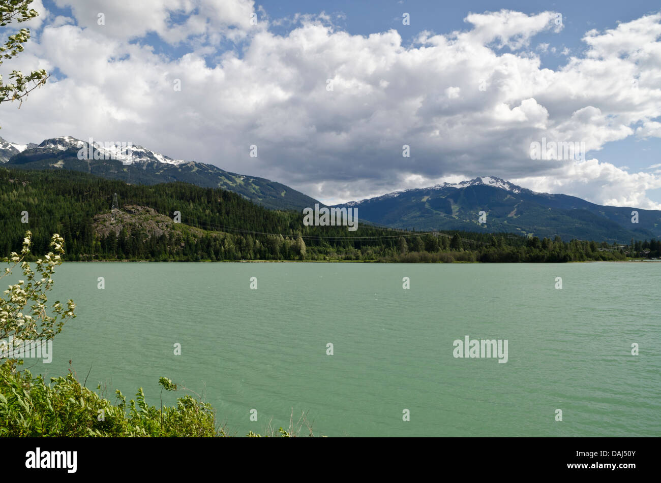 Green Lake in Whistler, British Columbia.  Whistler and Blackcomb mountains are in the distance. Stock Photo