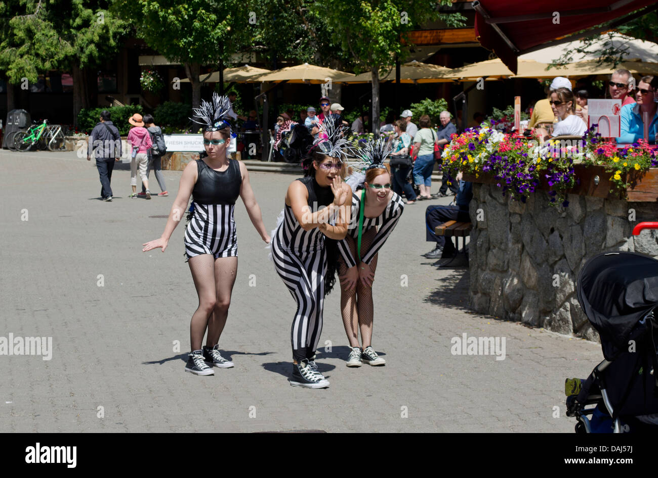 Three comical women street performers entertain visitors to Whistler Village, British Columbia Canada. - Stock Image