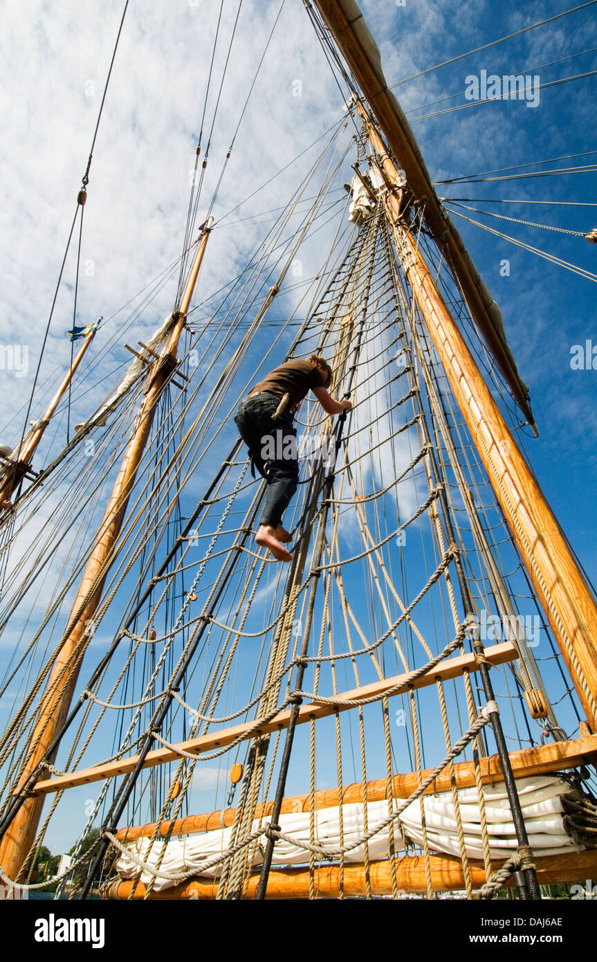 climbing the rigging tall ship ships boat boats sail sailing hoisting the sails working at height heights rope ropes - Stock Image