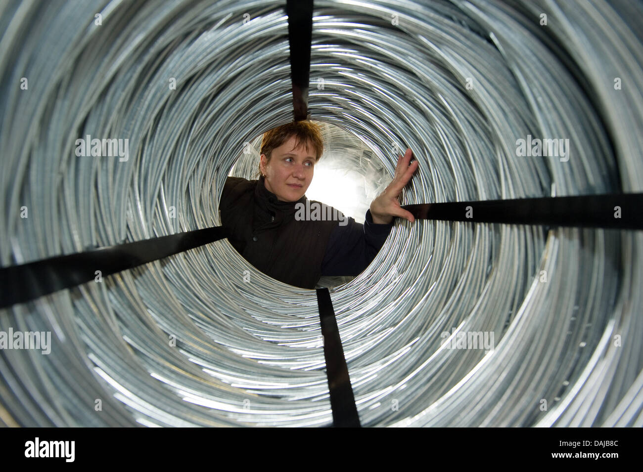 Elke Uekert from thecompany Doletzky Formdraht (Doletzky Shaping Wire) examines a spool of wire in Fuerstenwalde, - Stock Image