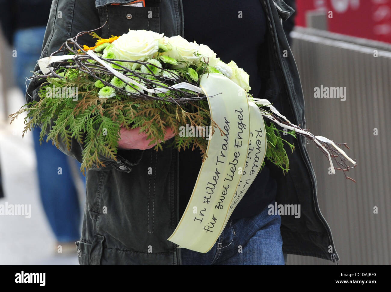 A mourner brings a wreath to the funeral service for the brutally murdered sisters Chiara (8) and Sharon (11), who - Stock Image