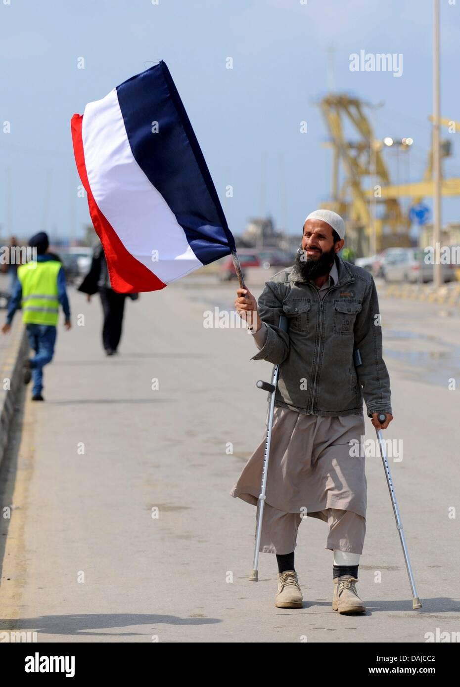 A man carries a French flag in rebel-held Benghazi, Libya, 03 April 2011. Libyan leader Muammar Al-Gaddafi continues - Stock Image