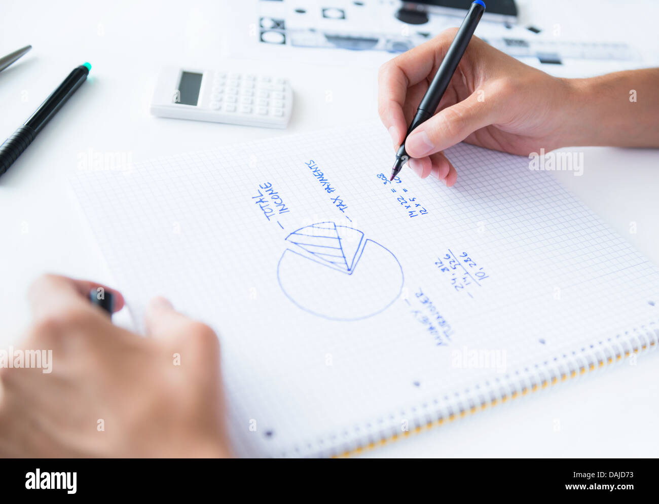 Person sitting at the desk, calculating home earnings and drawing circular diagram with numbers - Stock Image
