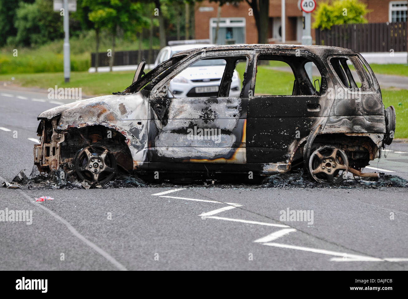 Newtownabbey, Northern Ireland. 15th July 2013 - A PSNI police car sits behind a burnt out car following riots in - Stock Image