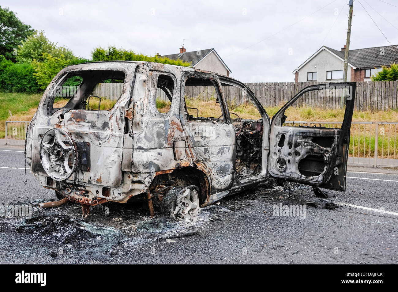 Newtownabbey, Northern Ireland. 15th July 2013 - A burnt out car blocks a major road following riots in Newtownabbey - Stock Image
